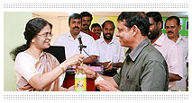 Mrs. Mini Mathew giving the first bottle of Virgin Plus to Sri Rajendran, Chairman, Horticorp